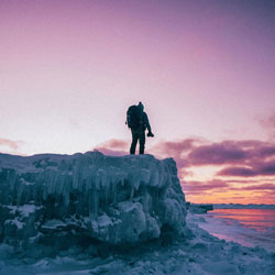 standing on the edge of a large chunk of ice, camera in hand, wearing a hiking backpack