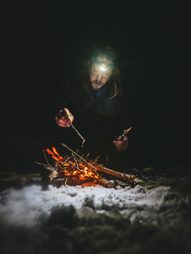 a camper tends to a fire in the snow, the image lit only by the glow of the fire and a beam of light from a headlamp